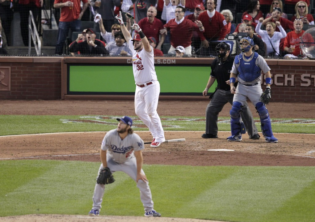 St. Louis Cardinals first baseman Matt Adams (32) celebrates as Los Angeles Dodgers starting pitcher Clayton Kershaw, front,  catch A.J. Ellis and umpire Eric Cooper watch his, three-run home run in the seventh inning of Game 4 of baseball's NL Division Series Tuesday, Oct. 7, 2014, in St. Louis. (AP Photo/Tom Gannam)