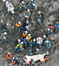 Rescuers struggle in the ash-covered muddy slope as they carry down the body of a newly-found victim from the summit of Mount Ontake in central Japan, Saturday, Oct. 4, 2014. Rescuers on Saturday retrieved four more bodies near the summit of the Japanese volcano that erupted last weekend, raising the death toll to 51, authorities said. (AP Photo/Kyodo News)