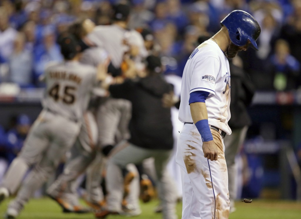 Kansas City Royals' Alex Gordon (4) walks off the field as San Francisco Giants players celebrates after Game 7 of baseball's World Series Wednesday, Oct. 29, 2014, in Kansas City, Mo. The Giants won 3-2 to win the series. (AP Photo/Charlie Neibergall)