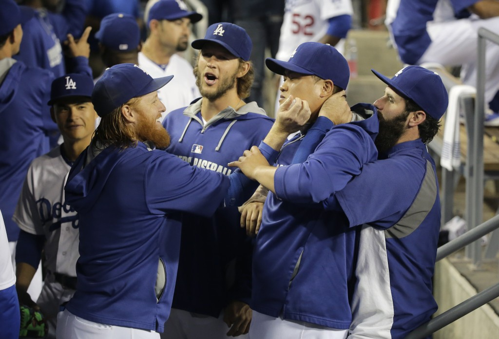Los Angeles Dodgers' Justin Turner, from left, pitcher Clayton Kershaw, pitcher Hyun-Jin Ryu, of South Korea, and Scott Van Slyke joke around in the dugout before a baseball game against the San Francisco Giants Monday, Sept. 22, 2014, in Los Angeles. (AP Photo/Jae C. Hong)