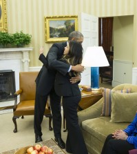 President Barack Obama hugs Ebola survivor Nina Pham in the Oval Office of the White House in Washington, Friday, Oct. 24, 2014. Pham, the first nurse diagnosed with Ebola after treating an infected man at a Dallas hospital is free of the virus. The 26-year-old Pham arrived last week at the NIH Clinical Center. She had been flown there from Texas Health Presbyterian Hospital Dallas. Pham's mother Diana, center, and sister Cathy Pham watch.  (AP Photo/Evan Vucci)