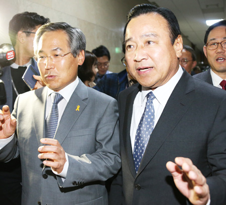Rep. Lee Wan-koo, right, floor leader of the ruling Saenuri Party, and his counterpart Woo Yoon-keun of the main opposition New Politics Alliance for Democracy walk out of a National Assembly conference room, Friday, after they agreed on three Sewol-related bills. (Yonhap)