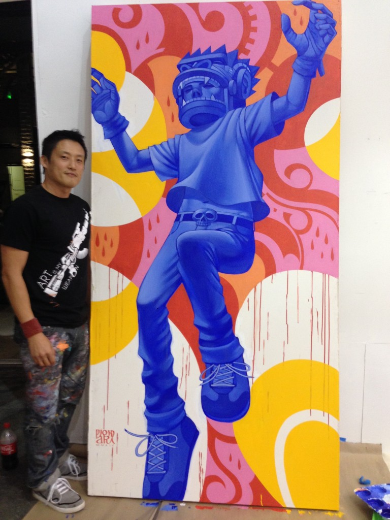 "Park stands next to a piece that is part of his latest series of paintings titled ""Gorilla Warfare"""