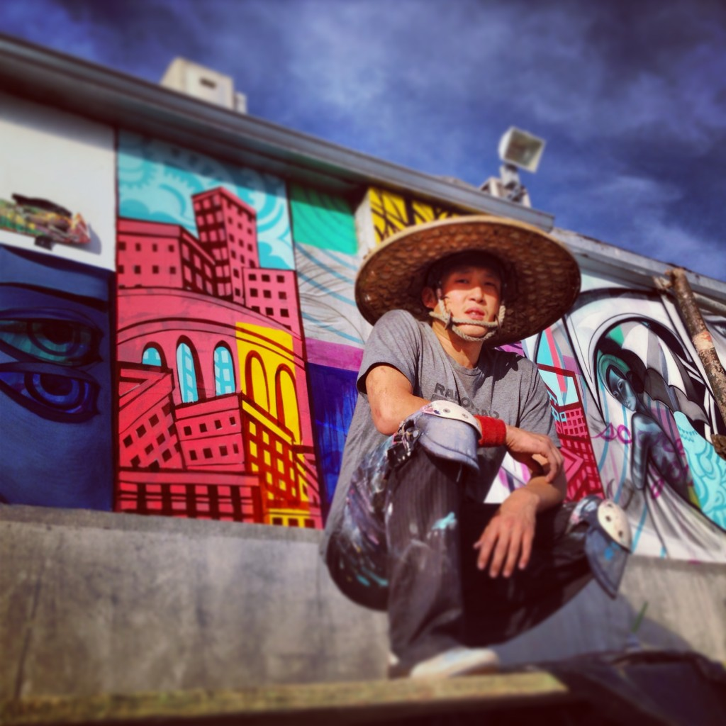 John Park crouching near a series of his own murals located in Los Angeles.