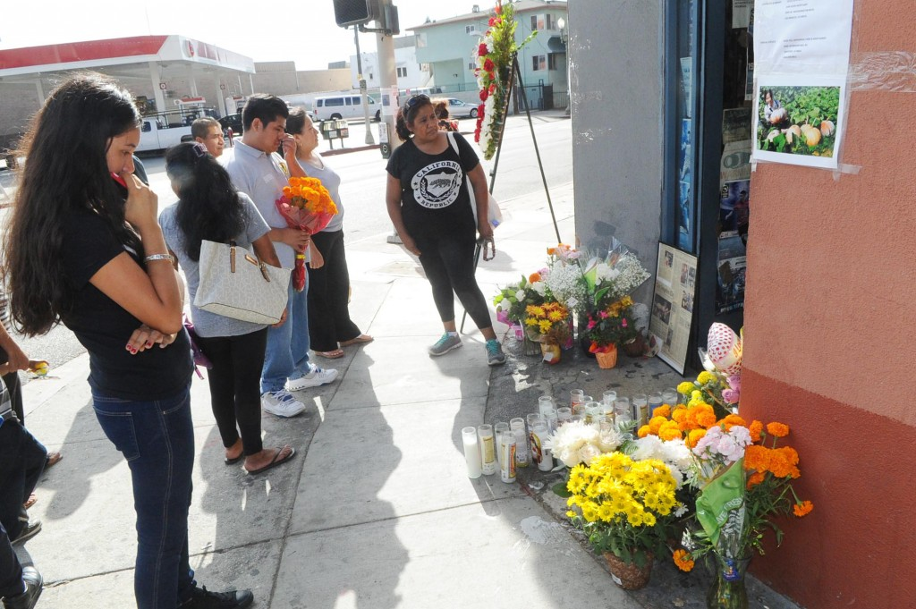 Mourners gather in front of OK Liquor in Los Angeles' Koreatown following Owner Lee Young-ok's death Thursday. (Park Sang-hyuk/The Korea Times)