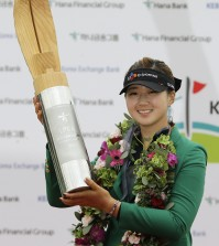 Kyu Jung Baek of South Korea poses with the trophy for the media after winning the KEB Hana Bank Championship golf tournament at Sky72 Golf Club in Incheon, South Korea, Sunday, Oct. 19, 2014. (AP Photo/Ahn Young-joon)