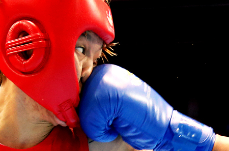 South Korean boxer Park Ji-na keeps her eyes open even as she is hit by Laishram Sarita Devi of India during their semifinals match in the women's under-60kg event at the Seonhak Gymnasium in Incheon Tuesday. Park won by decision. (Yonhap)