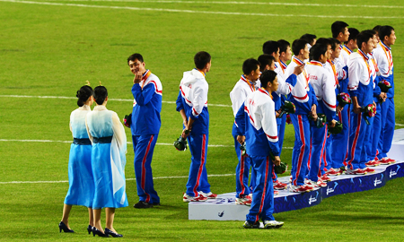 A North Korean football player talks to female staffers during an award ceremony at the Munhak Stadium in Incheon Thursday. North Korea won the silver medal after losing to South Korea 1-0 in the final game. (Korea Times photo by Shim Hyun-chul)