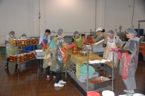 Volunteers make kimchi during the Northern California JABI Charity Association's event to give away free bottles to the area's elderly.