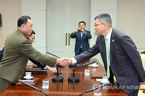 Ryu Je-seung, right, South Korea's Deputy Minister for National Defense Policy, and Kim Yong-chol, who leads North Korea's Reconnaissance General Bureau, shake hands before the military talks at the truce village of Panmunjom on Oct. 15, 2014. (Yonhap)