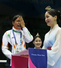 India's L. Sarita Devi cries standing beside bronze medalist Vietnam's Thi Duyen Luu after she refused her bronze medal during the medal ceremony for the women's light 60-kilogram division boxing at the 17th Asian Games in Incheon, South Korea, Wednesday, Oct. 1, 2014. India's protest against the outcome of an Asian Games boxing semifinal that was awarded to South Korea's Park Ji-na over Devi in the women's 60-kilogram division was rejected on Tuesday. Devi rejected her medal in protest against the result. (AP Photo/Kin Cheung)