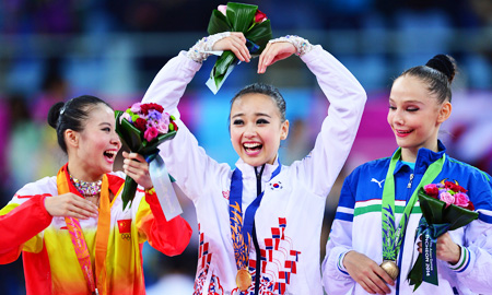 Son Yeon-jae, center, makes a heart-shape with her arms after winning South Korea's first-ever Asiad gold in the individual all-around event at the Namdong Gymnasium in Incheon, Thursday. China's Deng Senyue, left, won the silver, while Anastasiya Serdyukova of Uzbekistan settled for bronze. (Korea Times photo by Shim Hyun-chul)