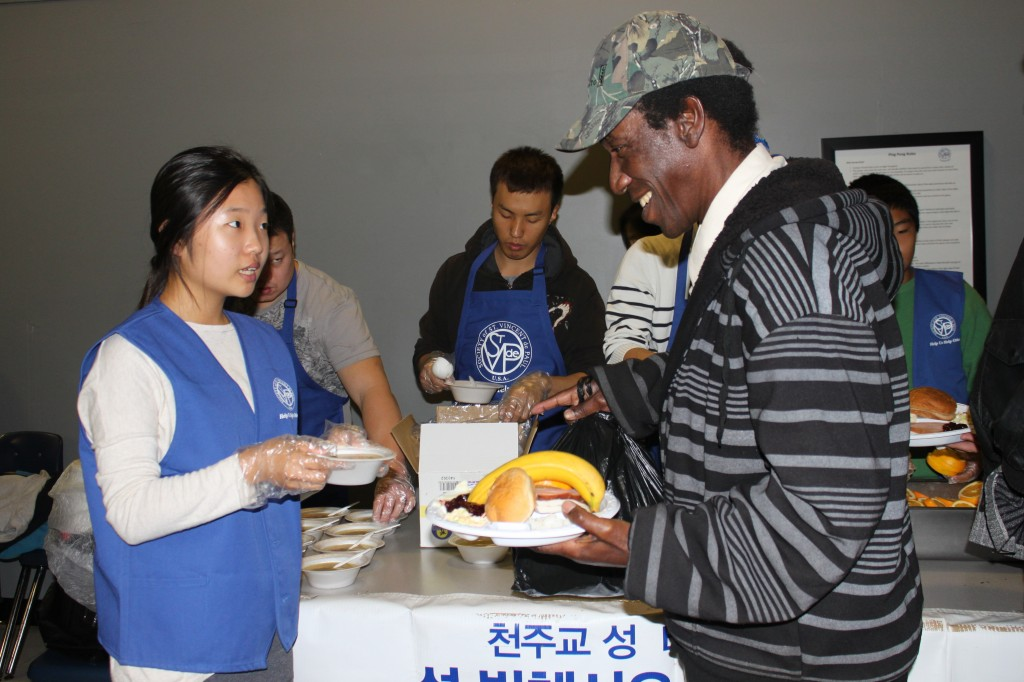 A Korean teenager serves homemade soup to a homeless man at the special Thanksgiving breakfast.