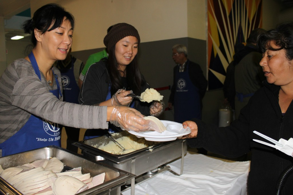 Korean women serve turkey and mashed potatoes to a homeless woman.