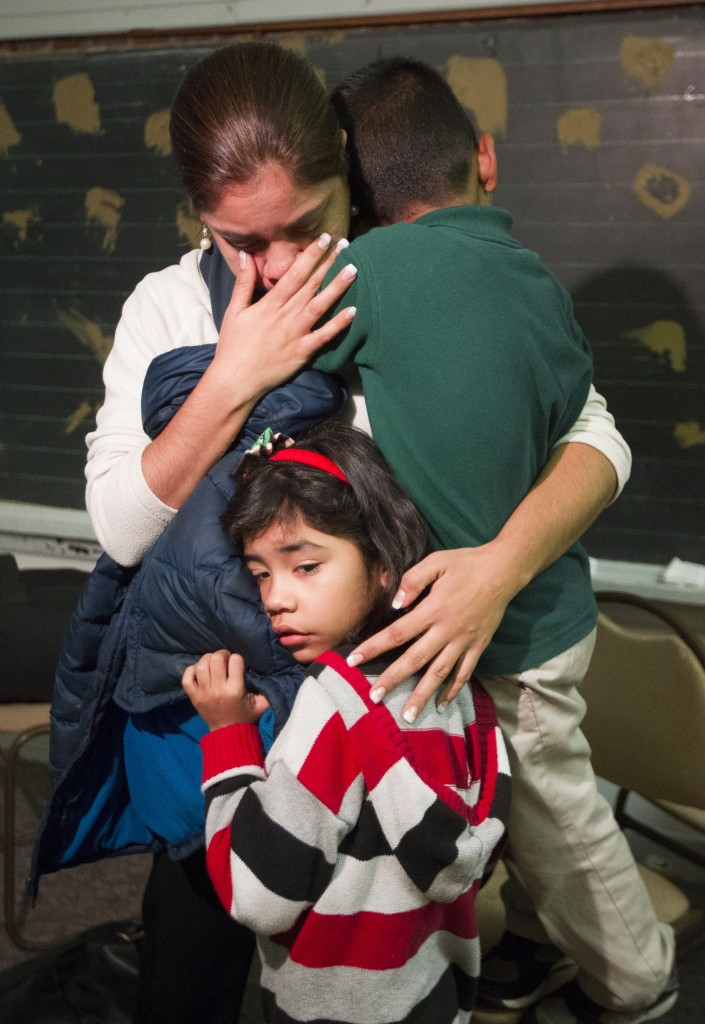 Isela Segovia hugs her two children Nivia, 7, bottom,  and Elian, 6, while watching President Obama's speech as it is televised Thursday, Nov. 20, 2014, in Houston. Obama's sweeping changes to the U.S. immigration system could shield nearly 5 million people here illegally from deportation, without going through Congress. (AP Photo/Houston Chronicle, J. Patric Schneider)