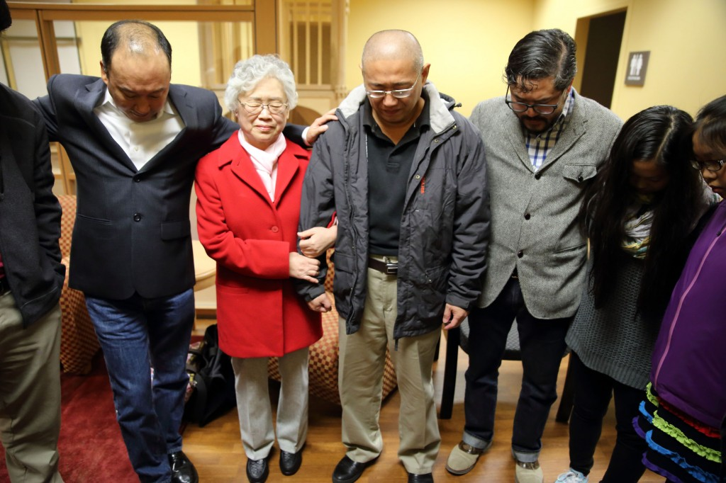 This photo provided by Derek Sciba shows Kenneth Bae, center, and his mother Myunghee Bae, in red coat, praying with other family members after his release from North Korea, Saturday Nov. 8, 2014.  (AP Photo/Derek Sciba)