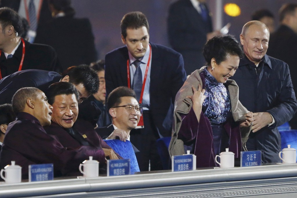 In this Nov. 10, 2014 file photo, Russia's President Vladimir Putin, right, puts a shawl on Peng Liyuan, second right, wife of Chinese President Xi Jinping, seated second left talking to U.S. President Barack Obama, left, as they arrive to watch a fireworks show after a welcome banquet for the Asia Pacific Economic Cooperation (APEC) summit in Beijing. It was a warm gesture on a chilly night when Vladimir Putin wrapped a shawl around the wife of Xi Jinping while the Chinese president chatted with Barack Obama. The only problem: Putin came off looking gallant, the Chinese summit host gauche and inattentive. (AP Photo, File)