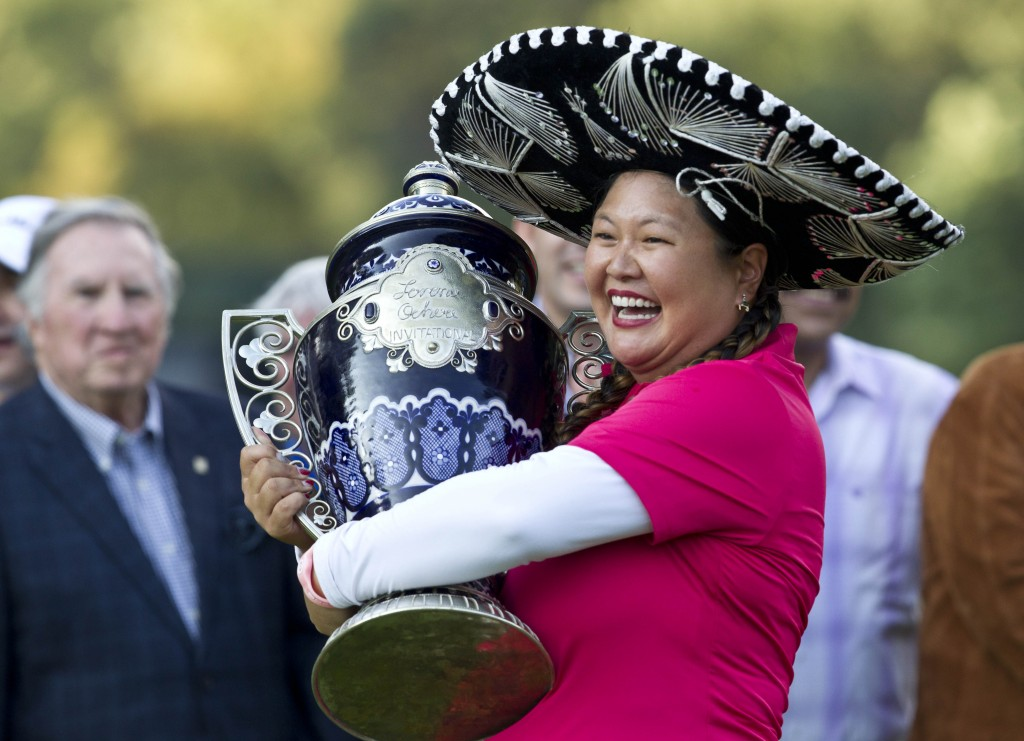 Christina Kim holds her trophy after winning the Lorena Ochoa Invitational LPGA golf tournament in Mexico City, Sunday, Nov. 16, 2014. Kim won the Invitational on Sunday for her first LPGA Tour title in nine years, beating China's Shanshan Feng in a playoff after blowing a five-stroke lead in the final round. (AP Photo/Christian Palma)