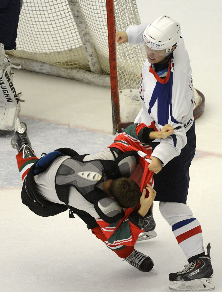 Csaba Kovacs, left, falls as he exchanges blows with Ahn Junghyun of South Korea during their ice hockey Four Nations Tournament first round match in Budapest, Hungary, Friday, Nov. 7, 2014. (AP Photo/MTI, Tamas Kovacs)