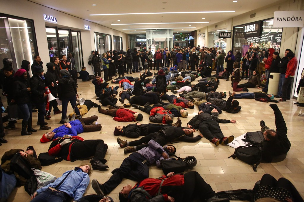 """Protestors gather inside of the Westlake Center in Seattle on Friday, Nov. 28, 2014, to protest the Ferguson grand jury decision. More than 200 protesters, some chanting """"Black Lives Matter!"""" tried to disrupt Black Friday shopping and downtown Seattle's traditional Christmas tree lighting ceremony. Police turned out in force, arresting five people, and a downtown mall closed early. (AP Photo/seattlepi.com, Joshua Trujillo)"""