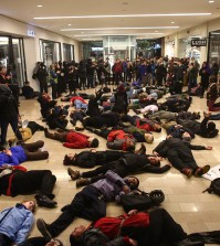 "Protestors gather inside of the Westlake Center in Seattle on Friday, Nov. 28, 2014, to protest the Ferguson grand jury decision. More than 200 protesters, some chanting ""Black Lives Matter!"" tried to disrupt Black Friday shopping and downtown Seattle's traditional Christmas tree lighting ceremony. Police turned out in force, arresting five people, and a downtown mall closed early. (AP Photo/seattlepi.com, Joshua Trujillo)"