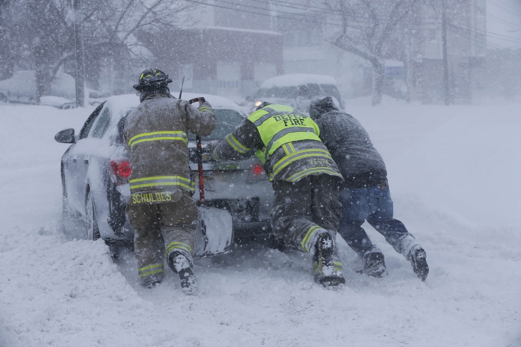 Firefighters from West End Hose Company in Depew, N.Y. help a stuck motorist on Transit Road, Tuesday, Nov. 18, 2014.  Several feet of lake-effect snow paralyzed the Buffalo area Tuesday, forcing state troopers to deliver blankets and other supplies to motorists stranded on the New York State Thruway and adding an ominous note to a wintry season that's already snarling travel and numbing fingers from the Midwest to the Carolinas.  (AP Photo/The Buffalo News, Derek Gee)