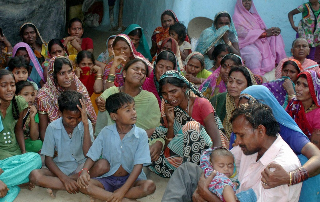 Relatives mourn the death of women who died after undergoing sterilization surgeries, at a village near Bilaspur, in the central Indian state of Chhattisgarh, Tuesday, Nov. 11, 2014. Eight Indian women have died and more than a dozen others in critical condition Tuesday after undergoing sterilization surgeries in a free government-run program to help slow the country's population growth. A total of 83 women, all poor villagers under the age of 32, had the operations Saturday in a hospital outside Bilaspur city. Each of the women had received a payment of 600 rupees, or about $10, to participate in the program, said the state's chief medical officer, Dr. S.K. Mandal. (AP Photo/Press Trust of India)