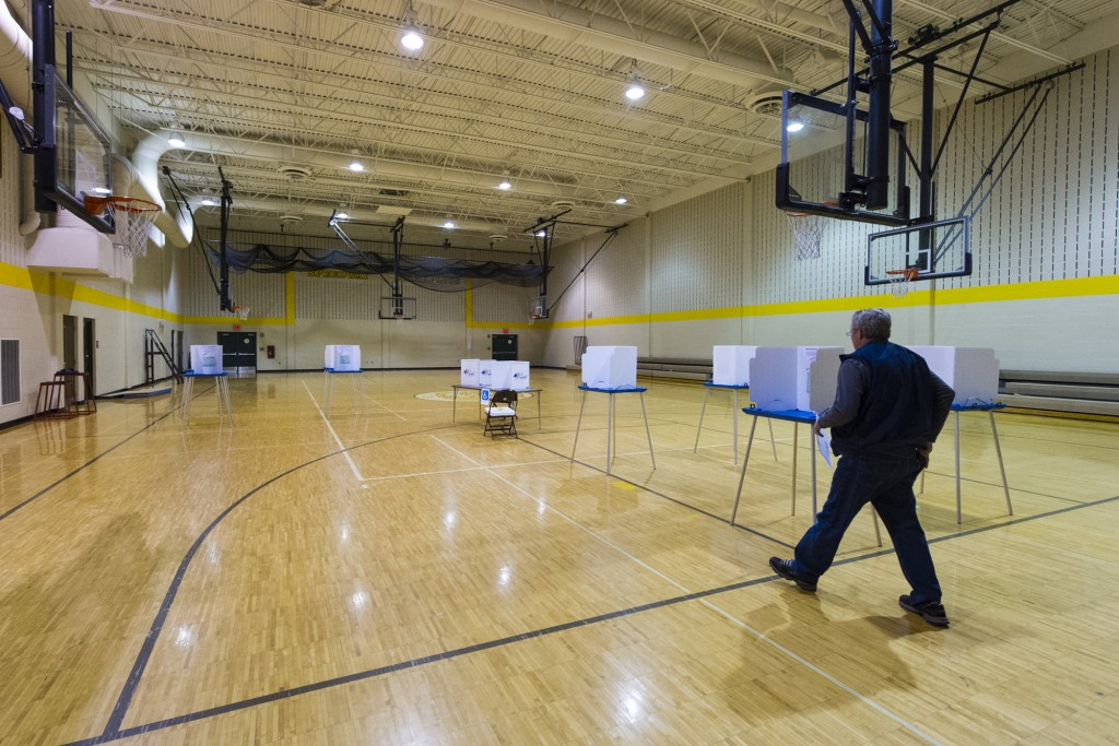 A voter heads to a voting booth with his ballot in hand at Speedway High School, Speedway, Ind., Tuesday, Nov. 4, 2014.  Record-low voter turnout could be the most notable development of the day as California is not faring much better. (AP Photo/Doug McSchooler)