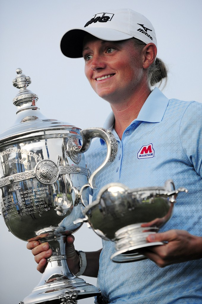 Stacy Lewis holds up her trophies for the media on hole 18, Sunday, Nov. 23, 2014 at the Tiburon Golf Club at the Ritz-Carlton Golf Resort in Naples, Fla. Lewis won LPGA Player of the Year and Vare trophies. This was her second consecutive Bare Trophy. She's the first American to win stroke average, money and POY since Betsy King in 1993. Today marked the final round of the LPGA's CME Group Tour Championship. Lydia Ko of New Zealand defeated Carlota Ciganda of Spain in a four-hole playoff. (AP Photo/Naples Daily News, Corey Perrine)