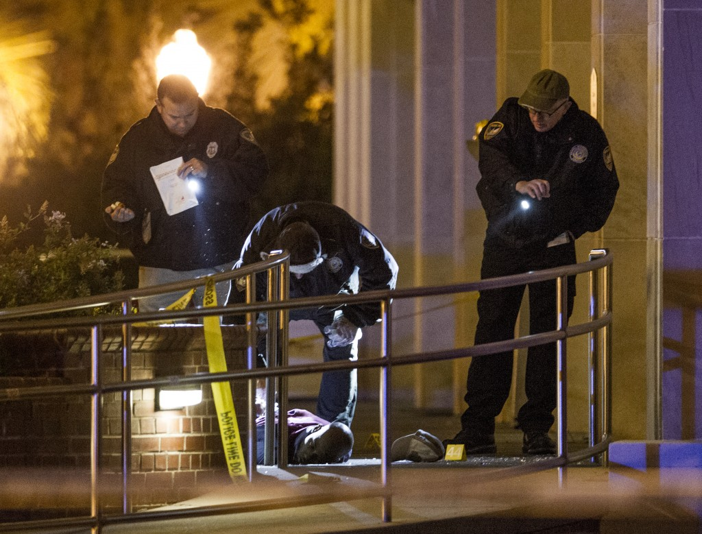 Tallahassee police investigate the scene of a shooting outside the Strozier library on the Florida State University campus in Tallahassee, Fla. Thursday Nov 20, 2014. Officers shot and killed the suspected gunman police said. It has been confirmed by authorities that the body in this image is that of the dead gunman. There were no other fatalities in the shooting. (AP Photo/Mark Wallheiser)