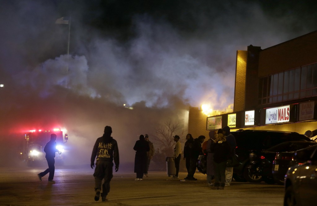 Smoke fills the streets as some buildings are on fire after the announcement of the grand jury decision Monday, Nov. 24, 2014, in Ferguson, Mo. A grand jury has decided not to indict Ferguson police officer Darren Wilson in the death of Michael Brown, the unarmed, black 18-year-old whose fatal shooting sparked sometimes violent protests. (AP Photo/Jeff Roberson)
