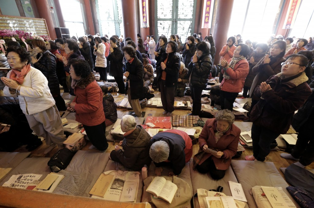 Parents pray to wish for their children' success in the Scholastic Aptitude Test at the Jogye Temple in Seoul, South Korea, Thursday, Nov. 13, 2104. About 640,000 high school students and graduates in South Korea are scheduled to take the examination Thursday that will virtually determine their admission to college. (AP Photo/Ahn Young-joon)