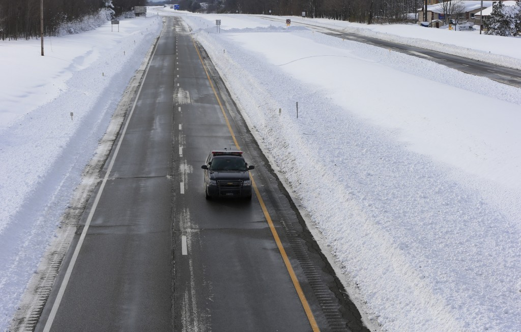 A law enforcement vehicle checks a closed New York State Thruway in Hamburg, N.Y. on Wednesday, Nov. 19, 2014.  A ferocious lake-effect storm left the Buffalo area buried under 6 feet of snow Wednesday, trapping people on highways and in homes, and another storm expected to drop 2 to 3 feet more was on its way. (AP Photo/The Buffalo News, Harry Scull Jr.)