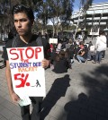 Several hundred UCSD students gathered on the walkway in front of Geisel Library in a sit-in to protest a proposed hike in tuition of up to five percent for the next five years. Andrew Villalobos carries a sign prior to a sti-in of UCSD students.  A senior graduating with a B.S. in engineering, he is worried about his brother and sister, both in high school and what this might mean for them if they choose to attend a UC school. ( AP - John Gastaldo/U-T San Diego/Zuma Press)