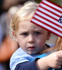 Parker Southerland, 1, waves a flag toward retired service dogs gathered at Pearson Park in Kinston, N.C., following a veteran's parade on Saturday, Nov. 8, 2014.(AP Photo/Daily Free Press, Zach Frailey)