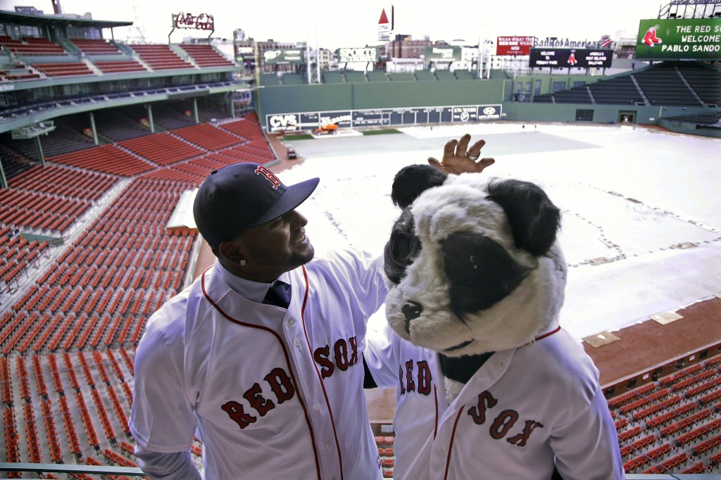 Newly acquired Boston Red Sox free agent third baseman Pablo Sandoval, nicknamed Kung Fu Panda, converses with a person dressed as a panda bear wearing a Red Sox jersey, overlooking a tarp covered Fenway Park field Tuesday, Nov. 25, 2014 in Boston. (AP Photo/Stephan Savoia)