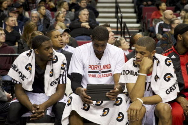 Wesley Matthews (from left), LaMarcus Aldridge and Nicolas Batum gather around an iPad on the bench. (Bruce Ely/The Oregonian)