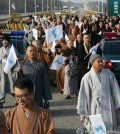 This file photo shows Buddhist priests attending the 17th annual conference of Buddhists of South Korea, China and Japan march for peace on a road near South Korea's border with North Korea, waving a flag symbolizing a reunified Korea. (Yonhap)