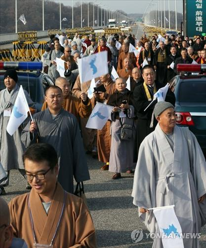 Buddhist priests attending the 17th annual conference of Buddhists of South Korea, China and Japan march for peace on a road near South Korea's border with North Korea, waving a flag symbolizing a reunified Korea. (Yonhap)