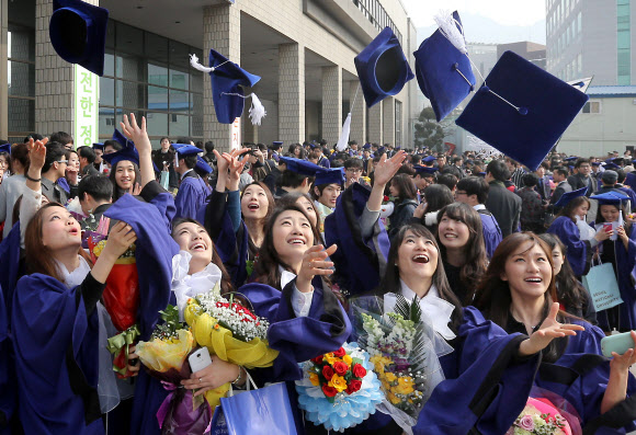 Graduates of Seoul National University throw their hats into the air after attending their graduation ceremony at the school in southern Seoul on Feb. 26, 2014. (Yonhap)