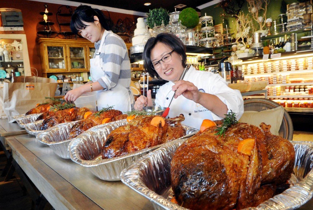 Banchan A La Carte Owner Jane Chang, right, and an employee prepare Thanksgiving turkeys ordered by Korean Americans Wednesday. (Park Sang-hyuk/The Korea Times)