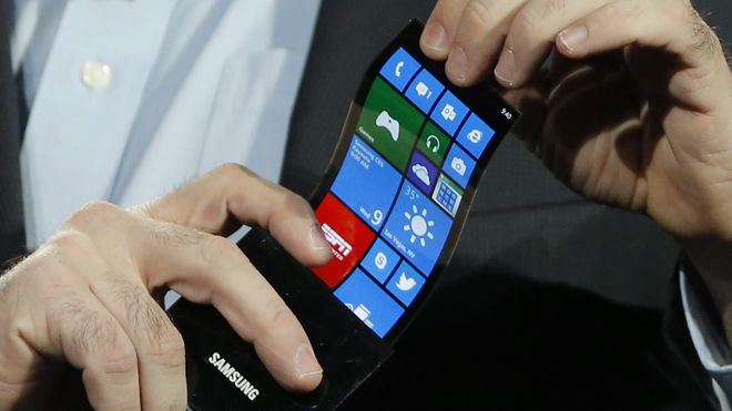 Jan. 9, 2013: Eric Rudder, chief technical strategy officer of Microsoft, holds a prototype Windows smartphone with a flexible OLED display during Samsung's keynote address at the International Consumer Electronics Show in Las Vegas. (AP Photo/Jae C. Hong)
