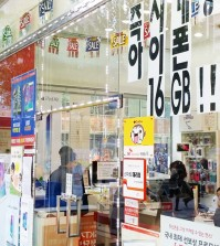 "Signs attached to the entrance wall of a mobile phone retail store in Jongno, central Seoul, that read, ""iPhone 6 is immediately available."" The nation's telecom watchdog threatened to take legal action against CEOs of local mobile carriers for disturbing the telecom market order by providing excessive subsidies for iPhone 6. ( Yonhap)"