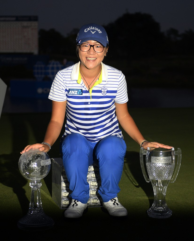 Lydia Ko poses with the Race to the CME Globe on the left, and CME Group Tour Championship trophy, right, while sitting on the one million prize money from the Globe trophy win, Sunday, Nov. 23, 2014 at the Tiburon Golf Club at the Ritz-Carlton Golf Resort in Naples, Fla. Today marked the final round of the LPGA's CME Group Tour Championship. Lydia Ko of New Zealand defeated Carlota Ciganda of Spain in a four-hole playoff. (AP Photo/Naples Daily News, Corey Perrine)