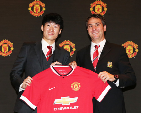 Manchester United Ambassador Park Ji-sung, left, and Jamie Reigle, Manchester United's managing director for the Asia Pacific, pose with a uniform at a media conference that took place at the Grand Hyatt Hotel, Seoul, Thursday. (Yonhap)