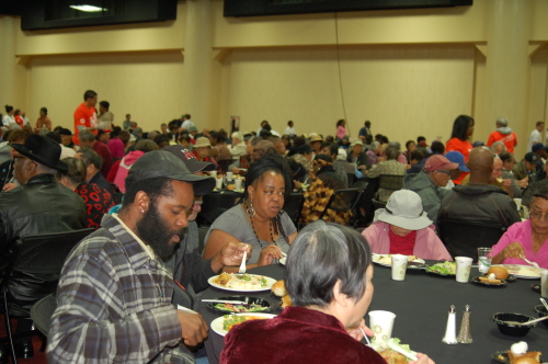 People eat a free Thanksgiving meal served at an annual event in Oakland's Marriott City Center Tuesday.