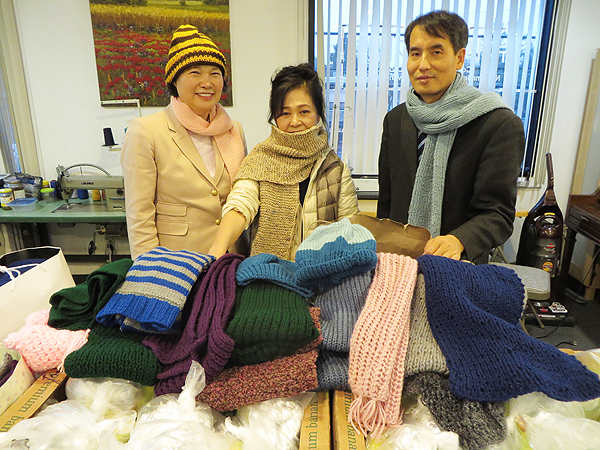 New Jersey ___ President Paul Yoon stands with center employees and hand-knitted scarves and hats to be given out to local homeless this Christmas.
