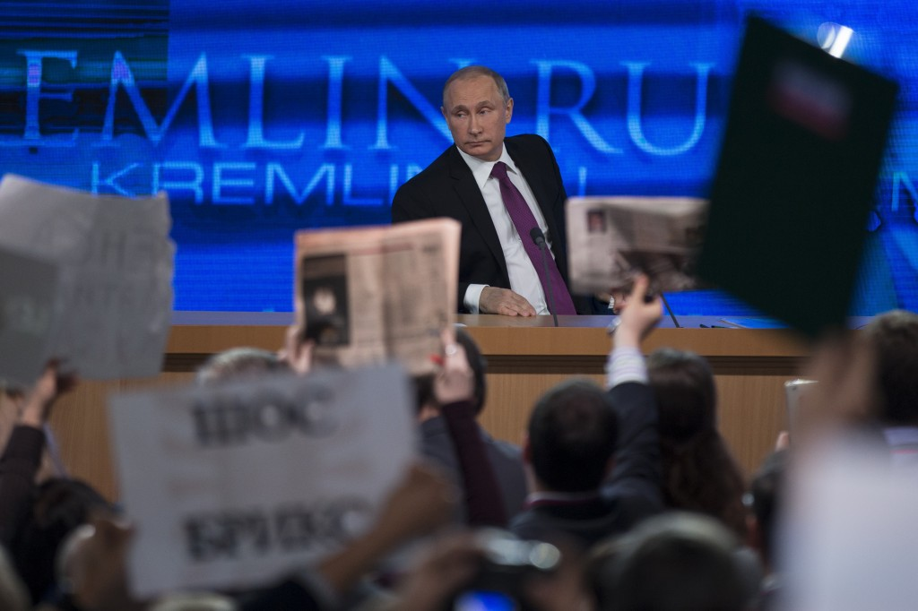 Journalists raise hands and posters and papers to attract attention, as Russian President Vladimir Putin, background, listens to a question, during his annual news conference in Moscow, Russia, Thursday, Dec. 18, 2014. The Russian economy will rebound and the ruble will stabilize, Russian President Vladimir Putin said Thursday at his annual press conference, he also said Ukraine must remain one political entity, voicing hope that the crisis could be solved through peace talks. (AP Photo/Pavel Golovkin)