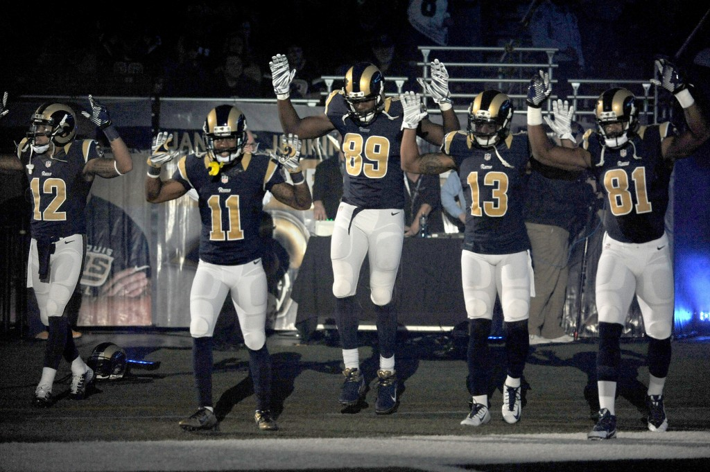 In this Sunday Nov. 30, 2014, file photo, St. Louis Rams players, from left; Stedman Bailey (12), Tavon Austin (11), Jared Cook, (89) Chris Givens (13) and Kenny Britt (81) raise their arms in awareness of the events in Ferguson, Mo.,  as they walk onto the field during introductions before an NFL football game against the Oakland Raiders in St. Louis. Time will tell whether the ``hands-up'' gesture during pregame introductions will leave a lasting memory or simply go down as a come-and-go moment in the age of the 24-hour news cycle. Either way, it certainly isn't the first time high-profile athletes have used their platform to make political statements. (AP Photo/L.G. Patterson, File)
