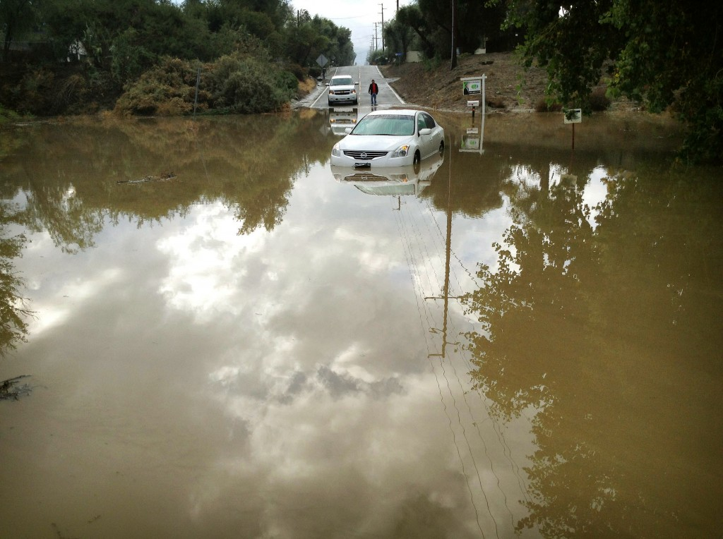 A car sits partially submerged in flood waters on Hemet Street in Hemet, Calif., Thursday morning, Dec. 4, 2014, after overnight rains doused the area.  A second day of much-needed rain is falling across drought-stricken California. (AP Photo/The Press-Enterprise, Craig Shultz )